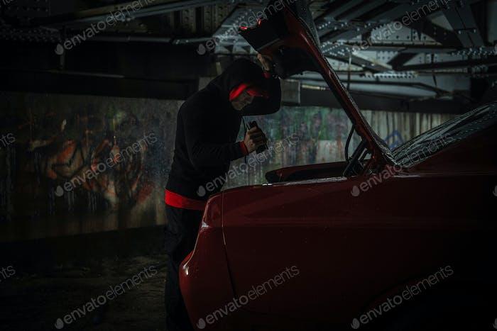 Ladrón caucásico mirando dentro del maletero del coche