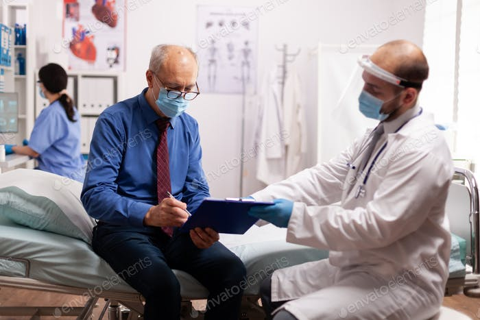 Elderly patient wearing face mask reading paperwork