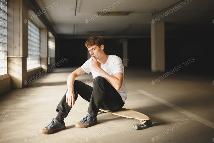 Portrait of boy with brown hair sitting on skateboard and thoughtfully looking down while smoking