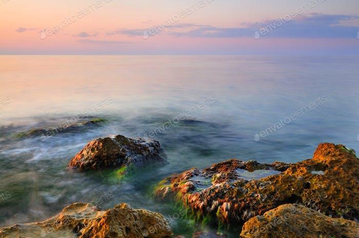Beautiful golden sunset over Black sea rocky coastline in Crimea