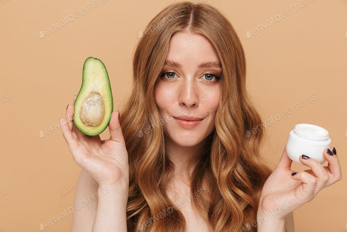 Portrait of young half-naked woman holding avocado and face cream jar