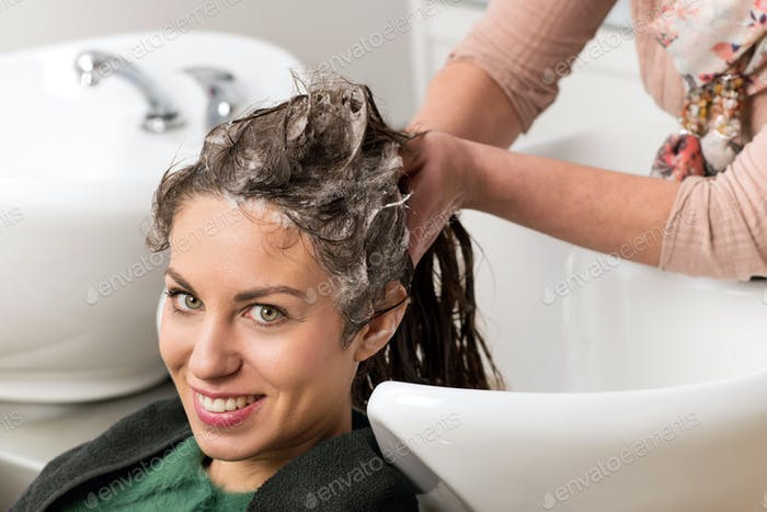 Attractive woman having her hair washed