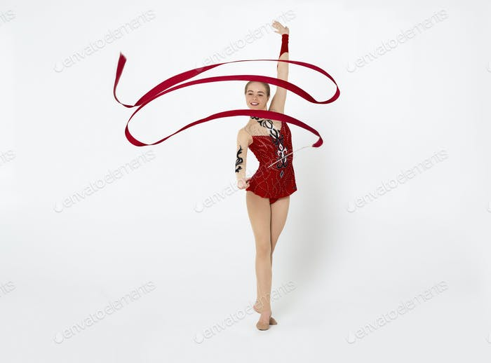 Professional gymnastics. Charming lady with string performing beautiful dance on white background