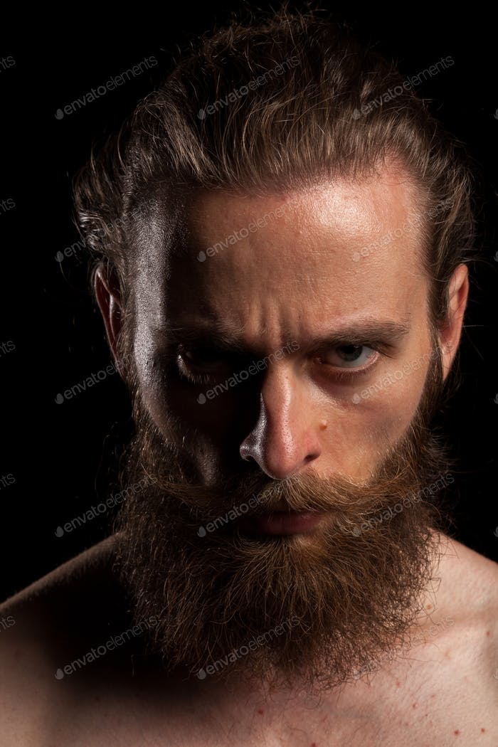 Tattooed bearded hipster on black background
