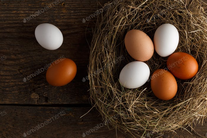 Chicken eggs in a nest on a wooden rustic background