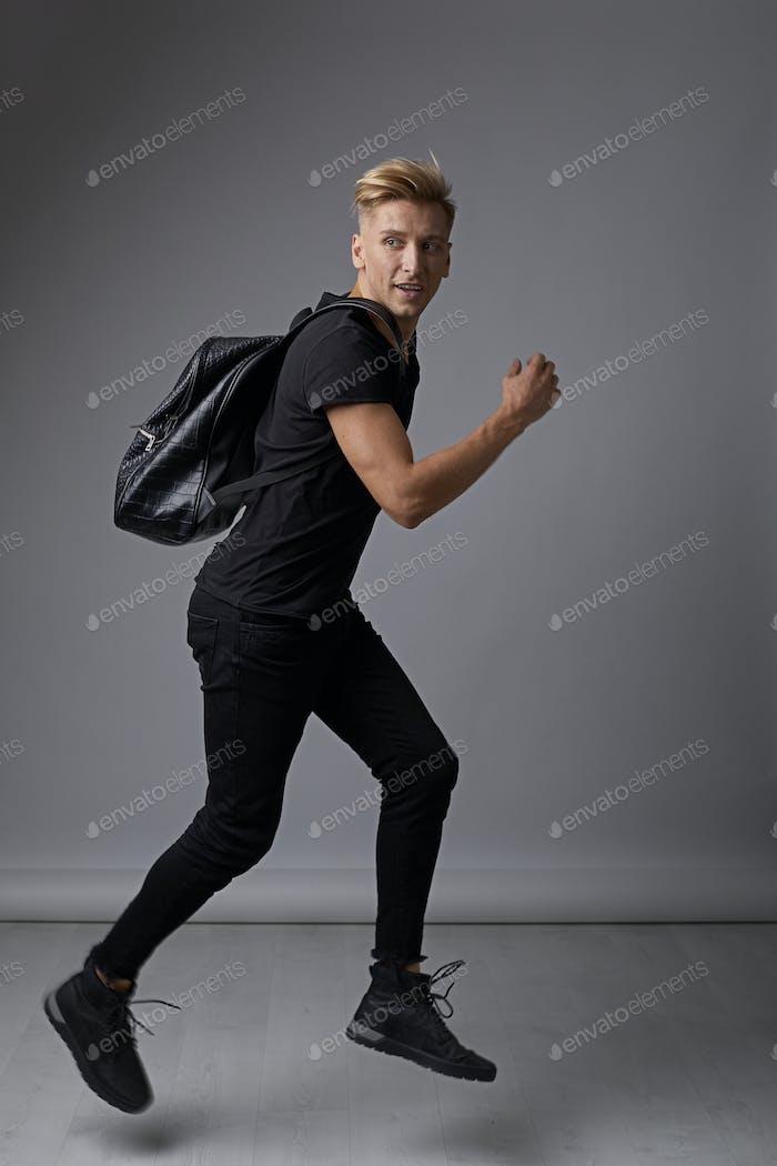 Schöner junger Mann läuft mit einem Rucksack auf Schultern