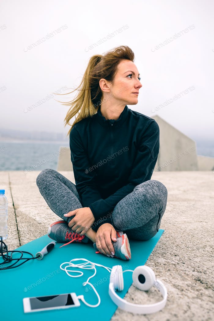 Woman sitting with sport accessories