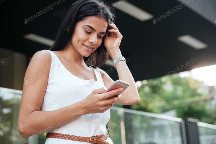 Happy woman using mobile phone outdoors