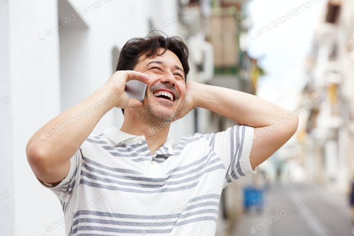 laughing middle aged man talking on smart phone