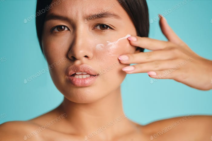 Close up attractive Asian brunette girl applying cream on clean skin intently looking in camera