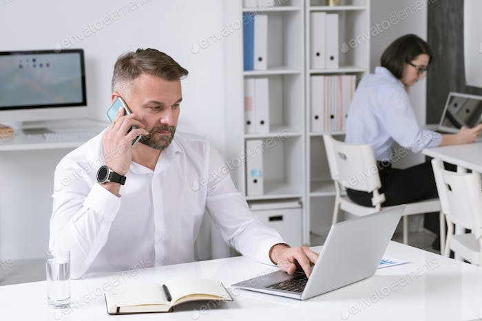 Serious mature businessman with smartphone talking to business partner