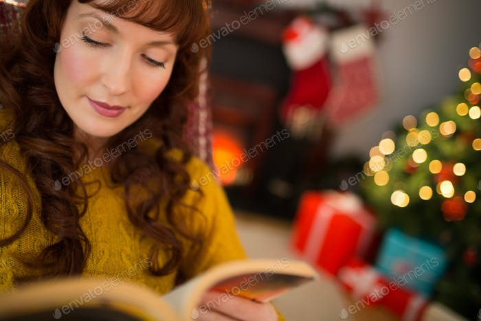 Calm redhead reading a book at christmas at home in the living room