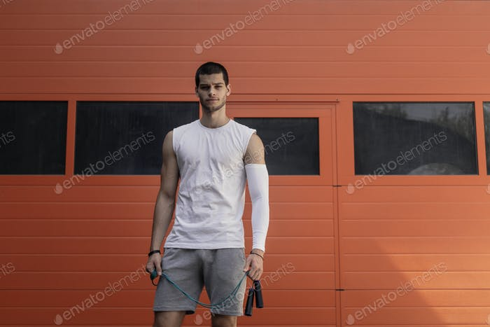 Portrait athletic, muscular man preparing for warming up with ju