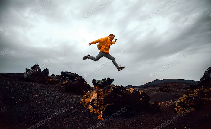 Hiker man jumping over the mountain. Freedom, risk, success and challenge. Focus on man