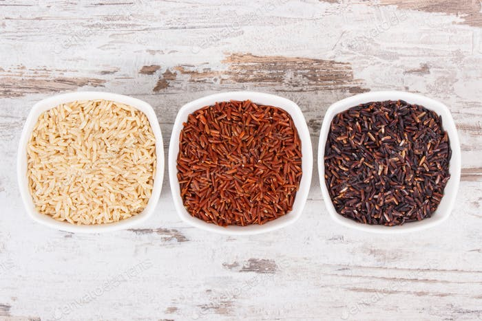 Black, red and brown rice in glass bowls, healthy nutrition concept