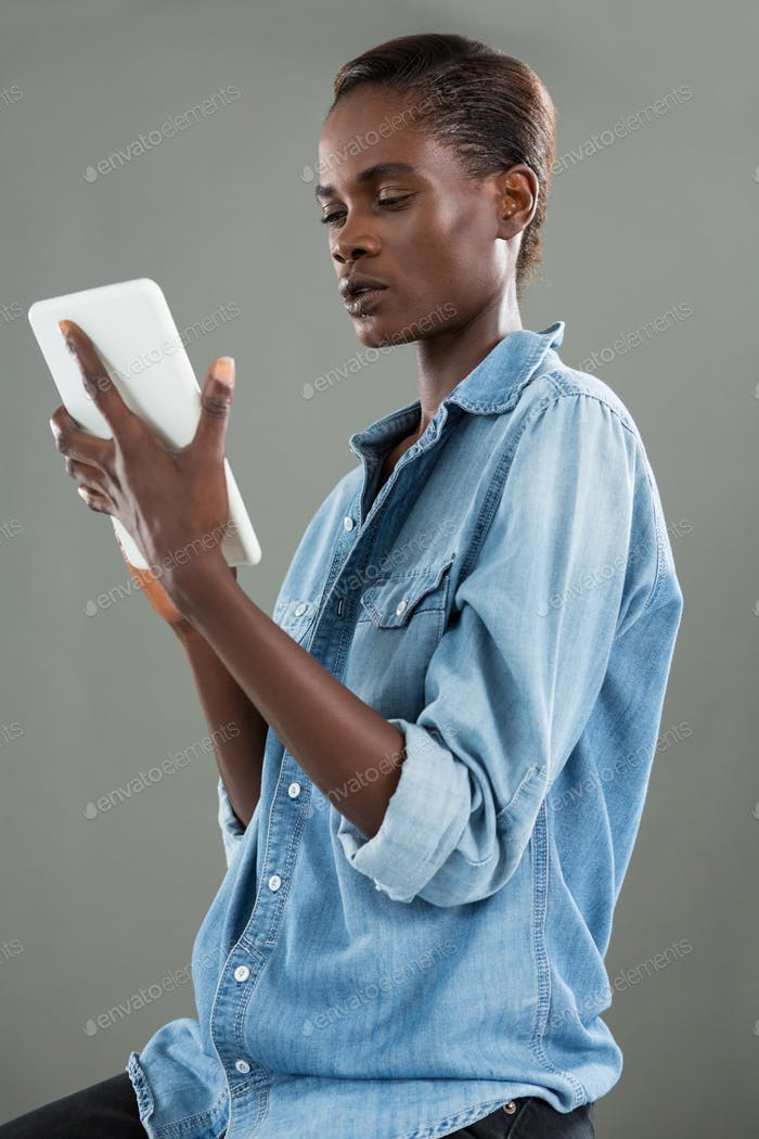 Androgynous man using digital tablet