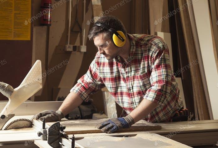 Arbeiter in Schutzbrille und Kopfhörer schneiden Holz in einem sa