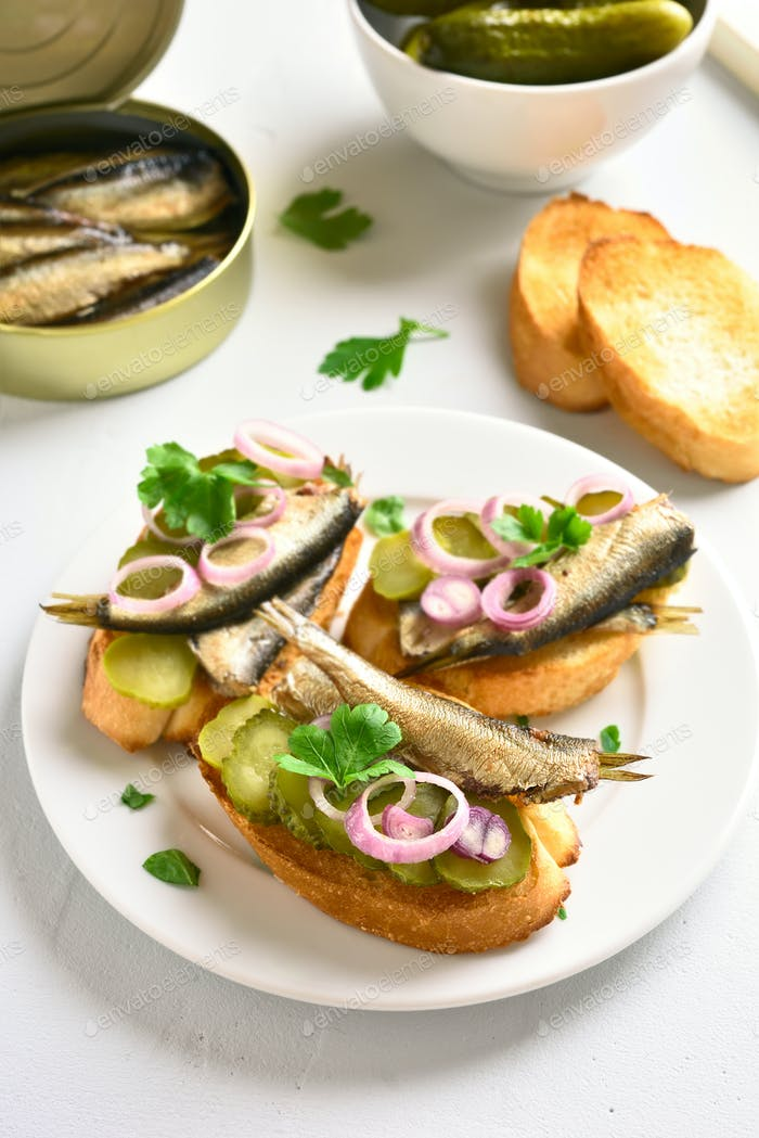 Sandwiches with sprats, marinated cucumber and onion