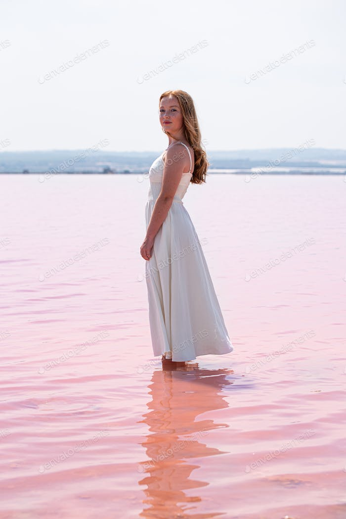 Side view of cute teenager woman wearing white dress standing on an amazing pink lake