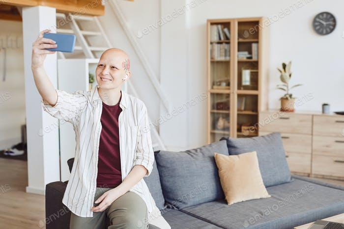 Contemporary Bald Woman Taking Selfie Photo at Home