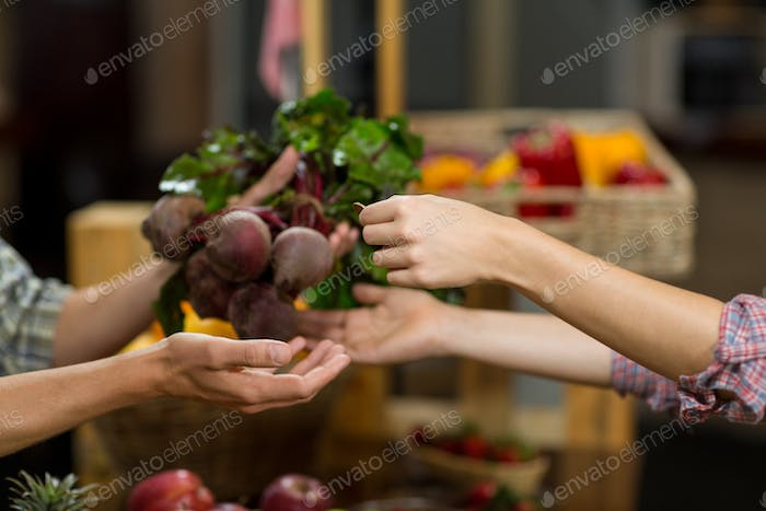 Woman buying beetroot from vendor in the grocery store