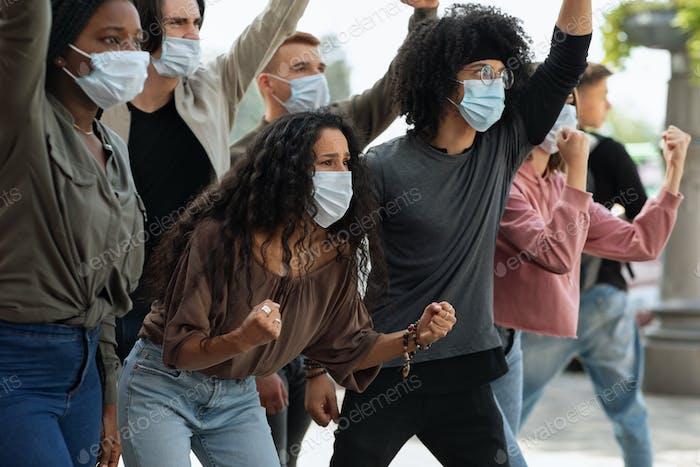 Jóvenes en máscaras faciales que asisten a la manifestación en la calle