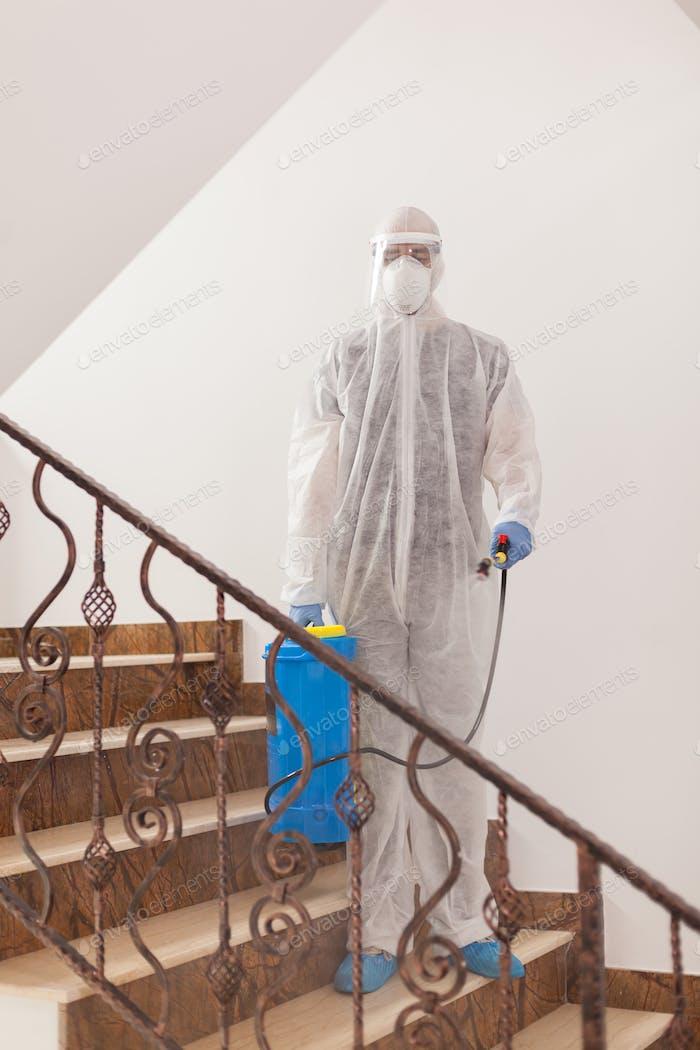 Desinfektionsmittel arbeiten im Schutzanzug