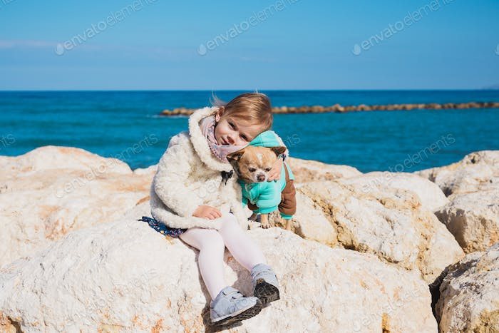 Little girl with chihuahua dog on seashore, outdoor summer