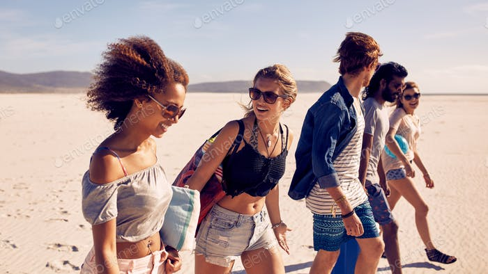 Group of young friends walking down a beach