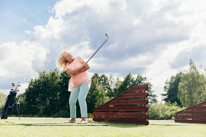 Senior active woman playing on a golf course.