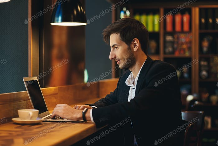 Portrait young confident businessman typing and  looking to lapt