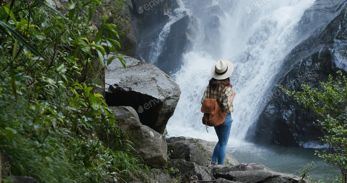 Woman goes hiking and loos at the waterfall in forest