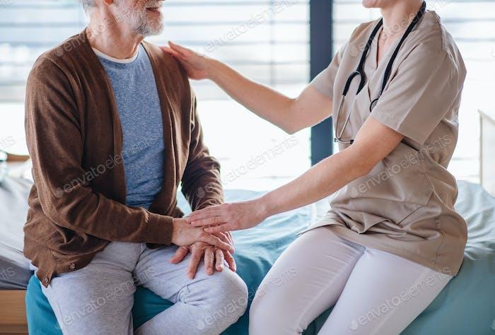 Eine Ärztin spricht mit älteren Patienten im Bett im Krankenhaus, Mittelteil.