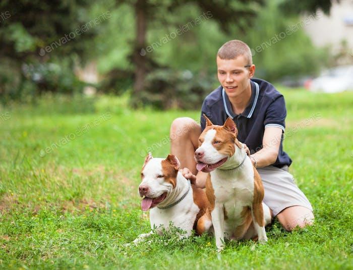 Joyful man sitting on grass with dogs