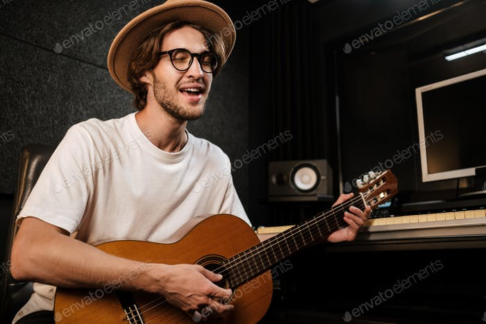 Attractive stylish man singing and playing on a guitar in music studio