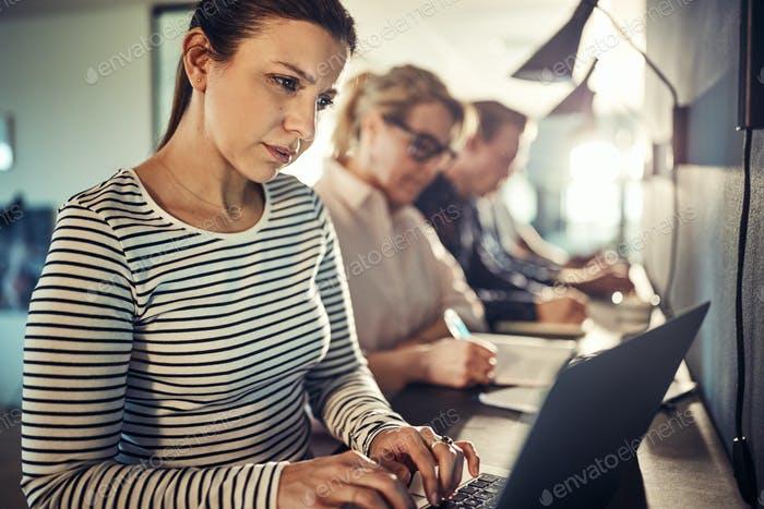 Focused young designer sitting with office colleagues using a laptop