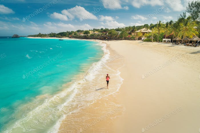 Aerial view of the running young woman on the white sandy beach
