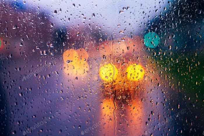 Wassertropfen von Regen auf blauem Glas Hintergrund. Straße Bokeh Ligh