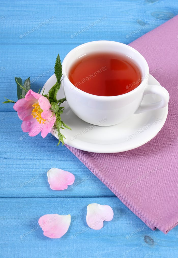 Cup of tea and wild rose flower on blue boards