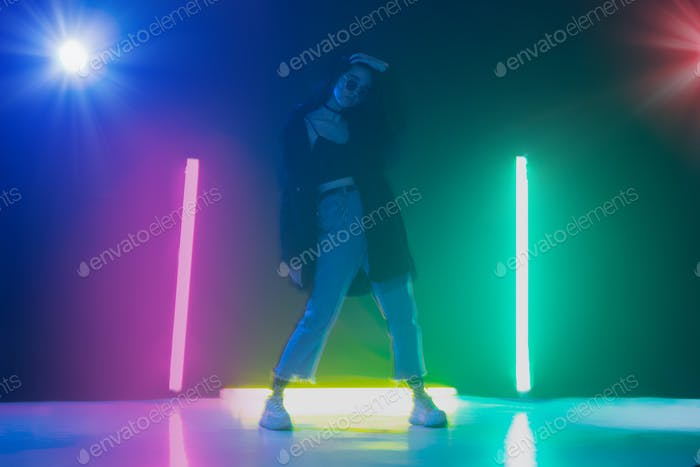 Young caucasian girl posing stylish in neon light on dark background