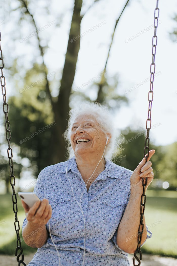 Cheerful senior woman listening to music at a playground