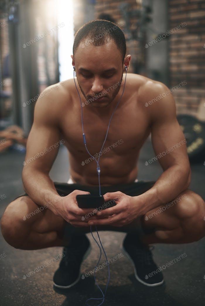 Hombre escuchando música en el teléfono celular en el gimnasio