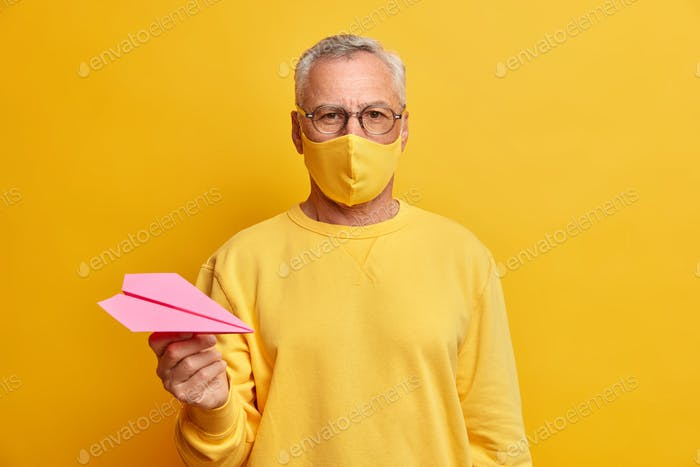 Serious grey haired man looks directly at camera wears transparent glasses protective mask and holds