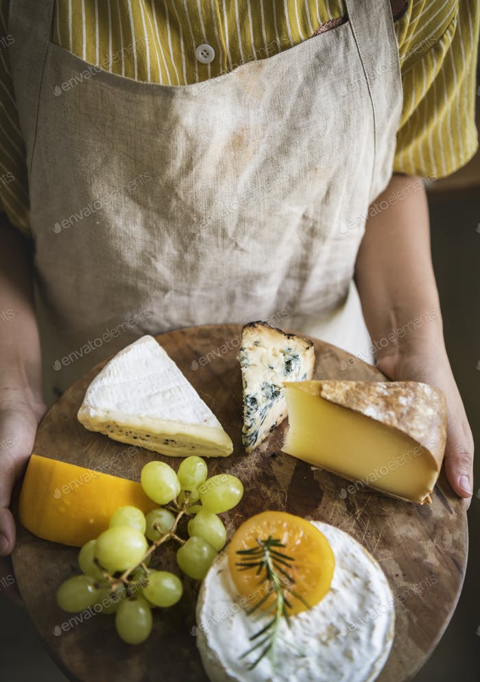 Person holding a platter of green grapes and different types of cheese