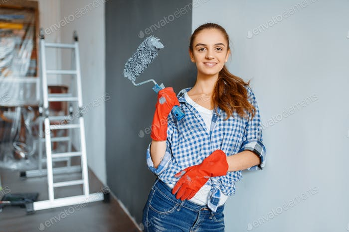 Female house painter in gloves paints the wall