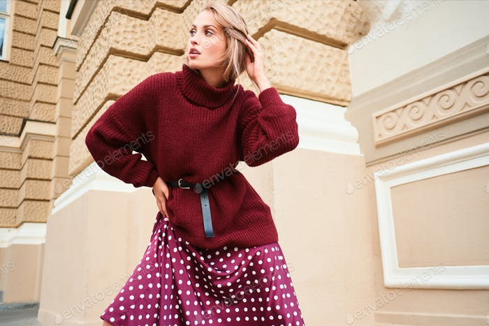 Gorgeous stylish blond girl in knitted sweater dreamily looking away sensually posing outdoor