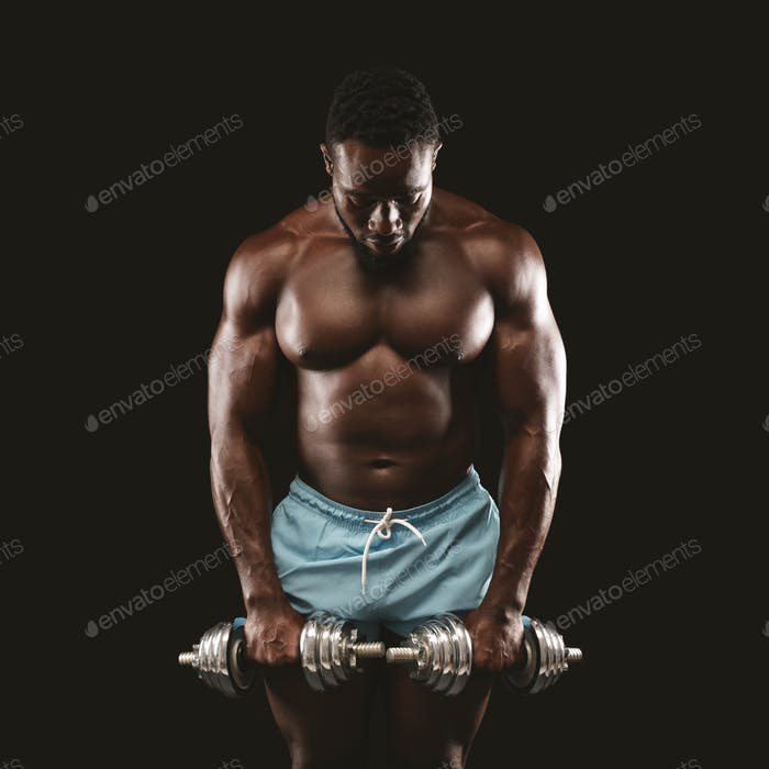 Portrait of black atlete holding dumbbells and looking down