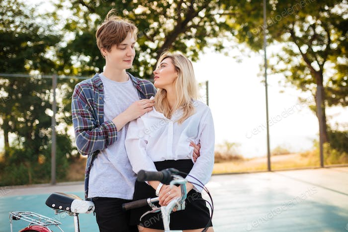 Beautiful girl with blond hair and boy dreamily looking on each other while standing in park