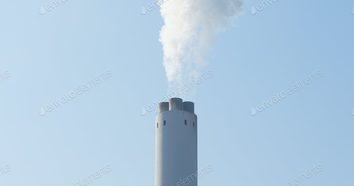 Chimney and smoke over blue sky
