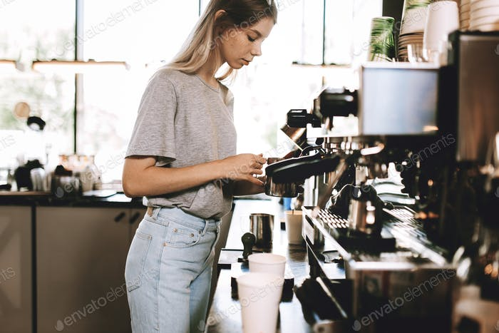 A young pretty thin blonde,dressed in casual outfit,is cooking coffee in a popular coffee shop